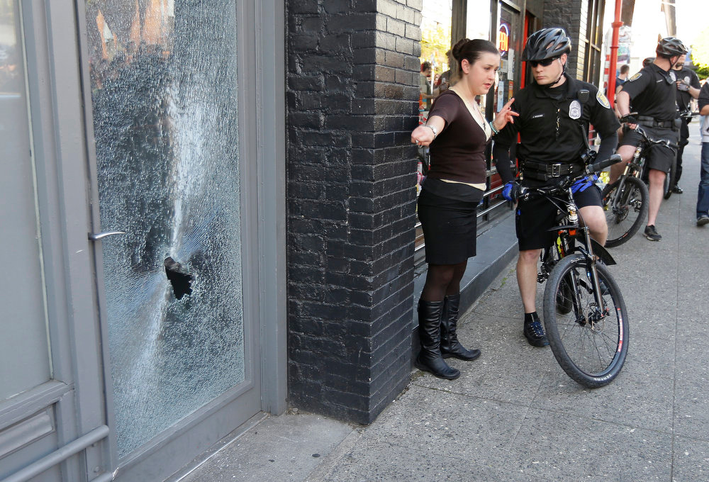 . A woman points out a broken window to a Seattle Police officer along the route of a May Day march that began as an anti-capitalism protest and turned into demonstrators clashing with police Wednesday, May 1, 2013, in downtown Seattle. (AP Photo/Ted S. Warren)