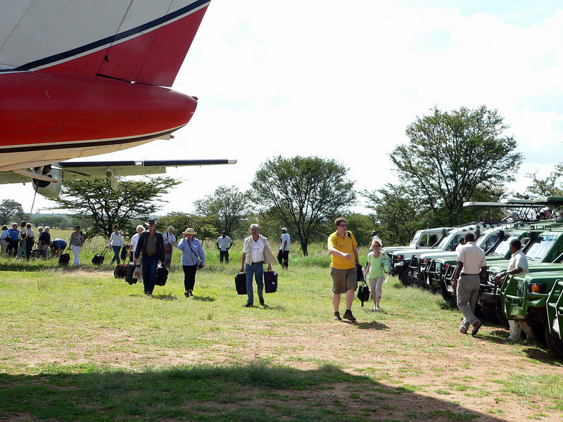 Disembarking our Air Kenya planes to head off to our lodges.  The group split here to go to either Migration Camp (that was us) or the Lobo Game Lodge.   The Lobo airstrip, where the two planes landed, was just a grass strip with wind socks at each end.