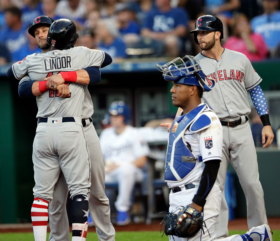 . Cleveland Indians\' Francisco Lindor (12) is congratulated by teammates Yan Gomes, left, and Tyler Naquin, right, after his grand slam during the fourth inning of a baseball game against the Kansas City Royals at Kauffman Stadium in Kansas City, Mo., Monday, July 2, 2018. Royals catcher Salvador Perez, second from left, waits for the next batter. (AP Photo/Orlin Wagner)