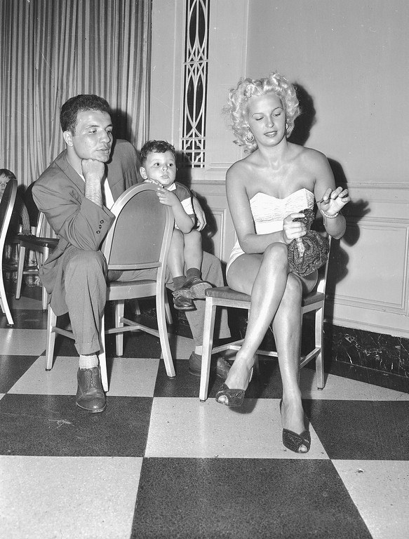 """. World Middleweight Champion Jake LaMotta holds his three-year-old son Jackie, while watching his wife Vicky practicing her crocheting skills in preparation for the upcoming \""""Mrs. New York City\"""" contest, on August 31, 1950 in New York City.  The champion  himself is scheduled to defend his title on September 13, in Detroit, Mich., against French boxer Laurent Dauthuille.  (AP Photo)"""