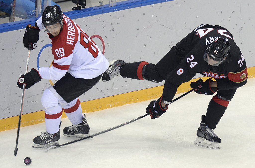 . Canada\'s Corey Perry (R) vies with Austria\'s Raphael Herburger during the Men\'s Ice Hockey Group B match Canada vs Austria at the Bolshoy Arena during the Sochi Winter Olympics on February 14, 2014.  AFP PHOTO / ALEXANDER NEMENOV/AFP/Getty Images