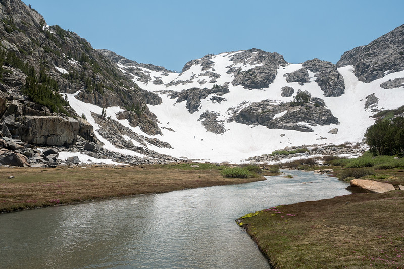 Two men and a dog descend a snowfield near the Palisade Glacier Trail