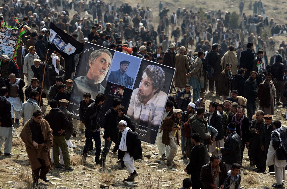 . Afghan supporters carry a poster bearing the image of former Afghan Vice-President Marshal Mohammad Qasim Fahim (C), formerly one of the country\'s most feared warlords, during his funeral on a hilltop in Kabul on March 11, 2014. (WAKIL KOHSAR/AFP/Getty Images)