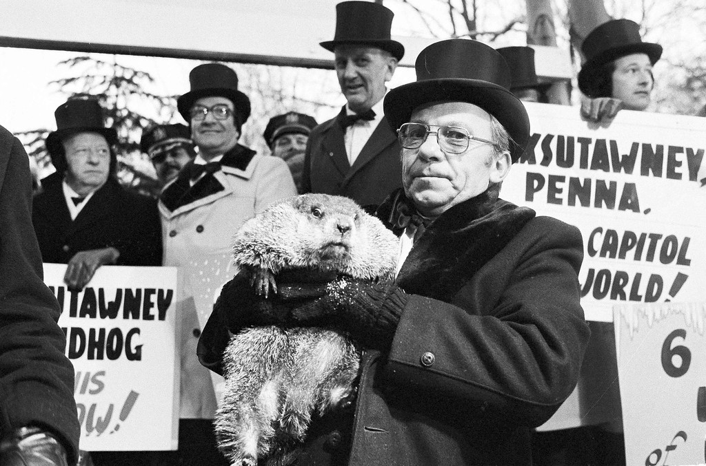 . Jim Means holds up a sleepy groundhog, Phil, at daybreak on Feb. 2, 1980, in Punxsutawney, Penn., in front of a crowd of anxious people. The groundhog saw his shadow and proclaimed six more weeks of winter. Means cares for Phil through the year in the animal\'s home in the town library. (AP Photo/Lucas)