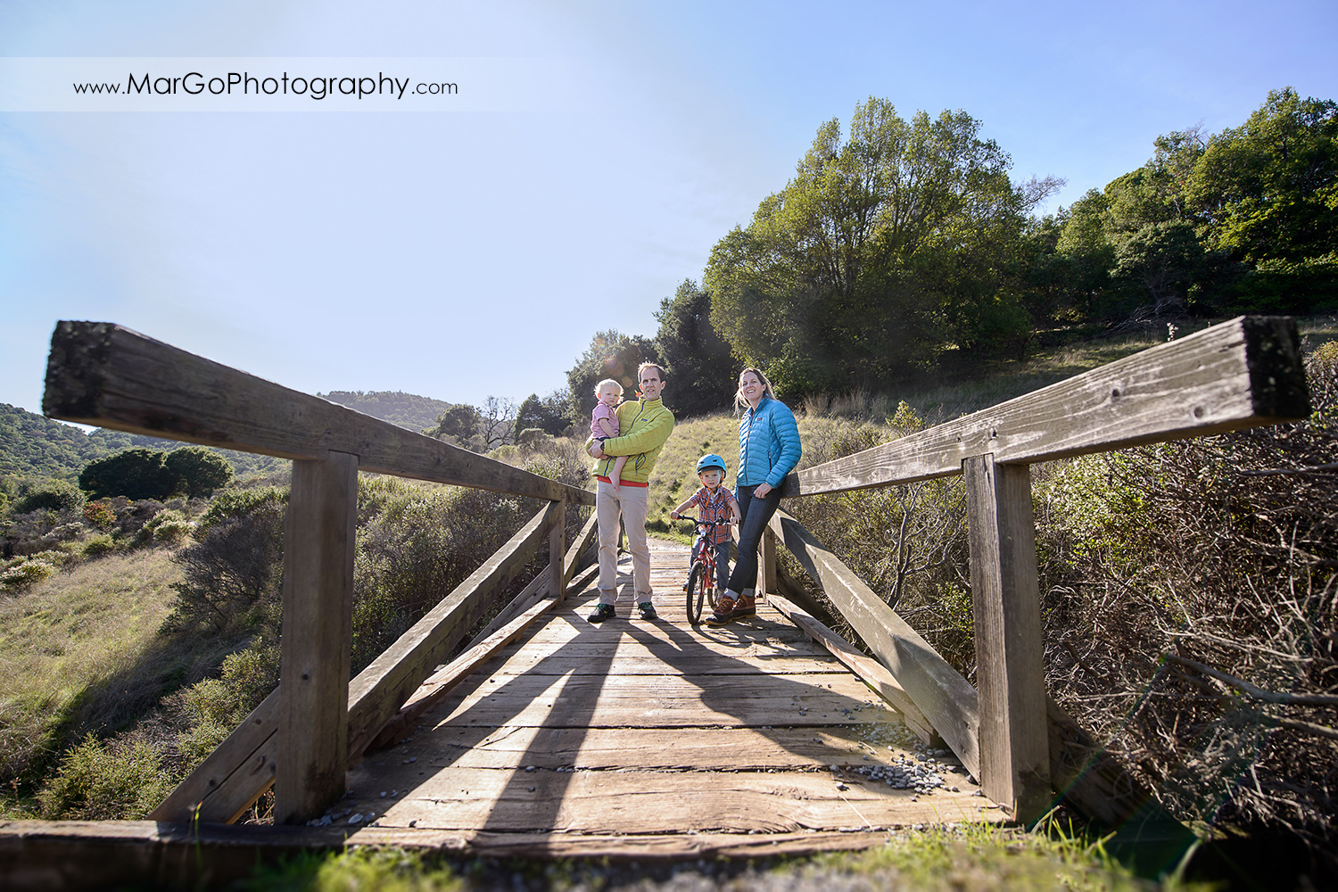 wide angle portrait of family of four on the wooden bridge at San Raeael China Camp SP
