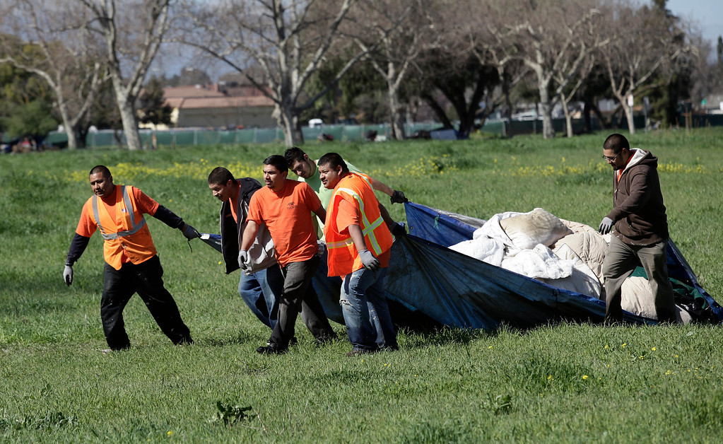 . A crew working for the city of San Jose hauls away debris from a homeless encampment on Spring St. in San Jose, Calif. on Friday, March 8, 2013. The encampment has grown to over 100 people in the last six months. Most of the people relocated to this area after cleanup efforts took place in other parts of the city.  (Gary Reyes/ Staff)