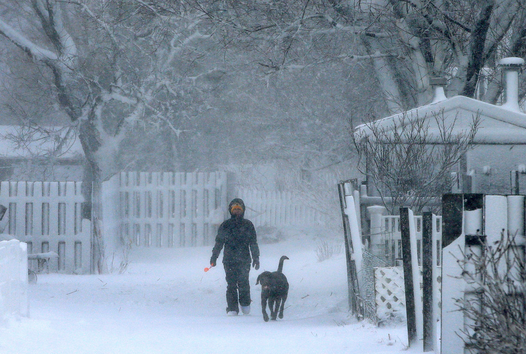 . Whitney Eakin, of Scituate, Mass., walks with her Labrador mix dog named Rudder, during a winter storm, Tuesday, March 13, 2018, in Scituate. The nor\'easter is expected to deliver up to 2 feet of snow to some areas of New England. (AP Photo/Steven Senne)