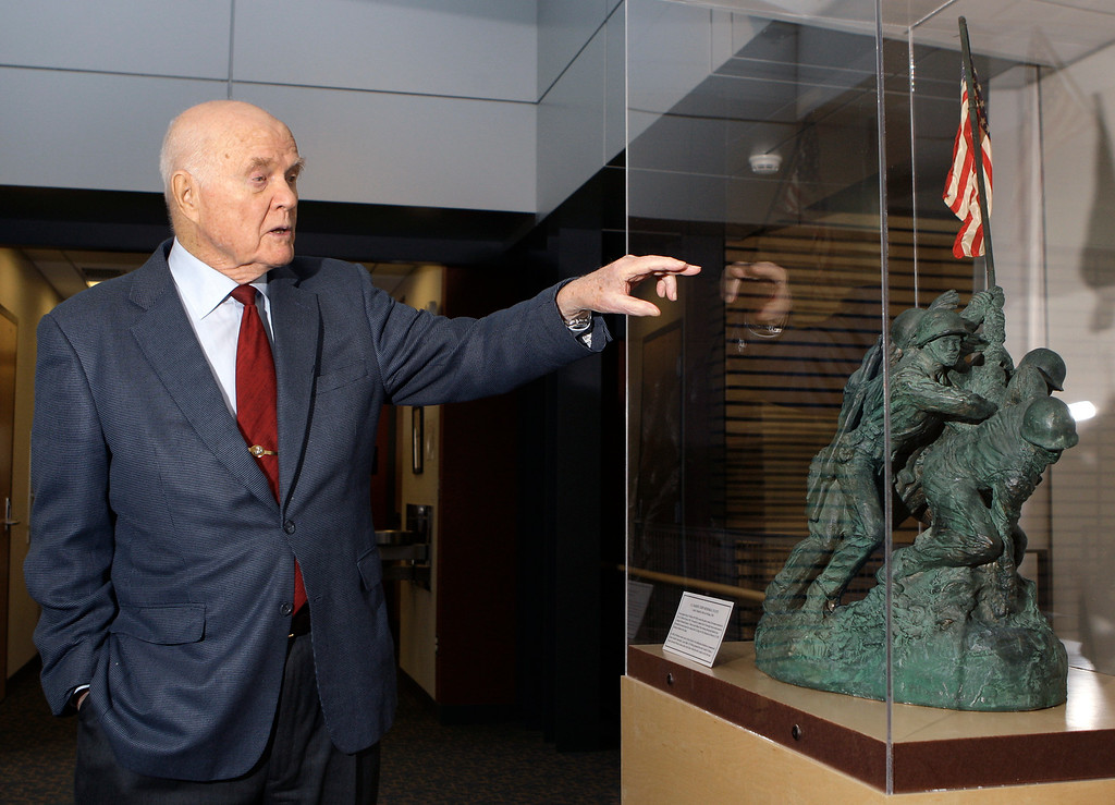. In this Jan. 25, 2012 photo, Sen. John Glenn talks about a replica of the U.S. Marine Corp Memorial Statue, given to him by the artist, while touring his office in Columbus, Ohio. Glenn was the first American to orbit Earth, piloting Friendship 7 around the planet three times in 1962. Glenn, as a U.S. senator at age 77, also became the oldest person in space by orbiting Earth with six astronauts aboard shuttle Discovery in 1998. (AP Photo/Jay LaPrete)