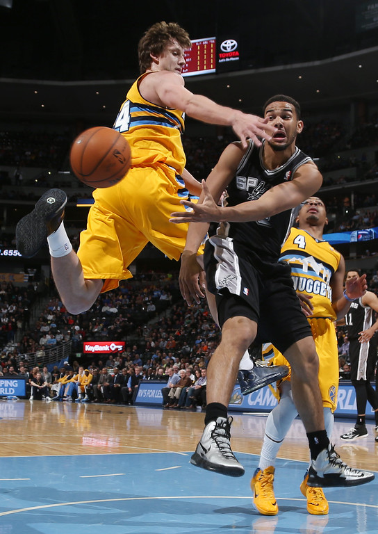 . San Antonio Spurs guard Cory Joseph, right, passes ball as he drives the lane past Denver Nuggets forward Jan Vesely, of the Czech Republic, in the fourth quarter of the Spurs\' 133-102 victory in an NBA basketball game in Denver, Friday, March 28, 2014. (AP Photo/David Zalubowski)