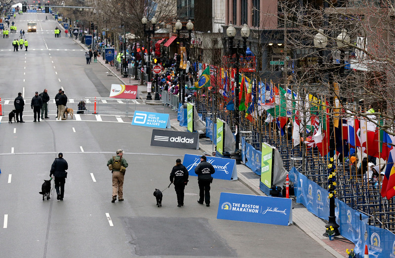 . Police flank an explosive ordnance disposal officer, second from left, as they patrol past the site of the first 2013 bombing site before the start of the Boston Marathon Monday, April 20, 2015 in Boston. (AP Photo/Charles Krupa)