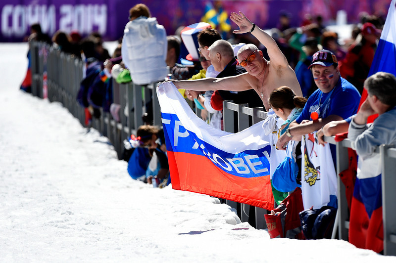 . A shirtless fan holds up a flag during the Women\'s 10 km Classic during day six of the Sochi 2014 Winter Olympics at Laura Cross-country Ski & Biathlon Center on February 13, 2014 in Sochi, Russia.  (Photo by Lars Baron/Getty Images)