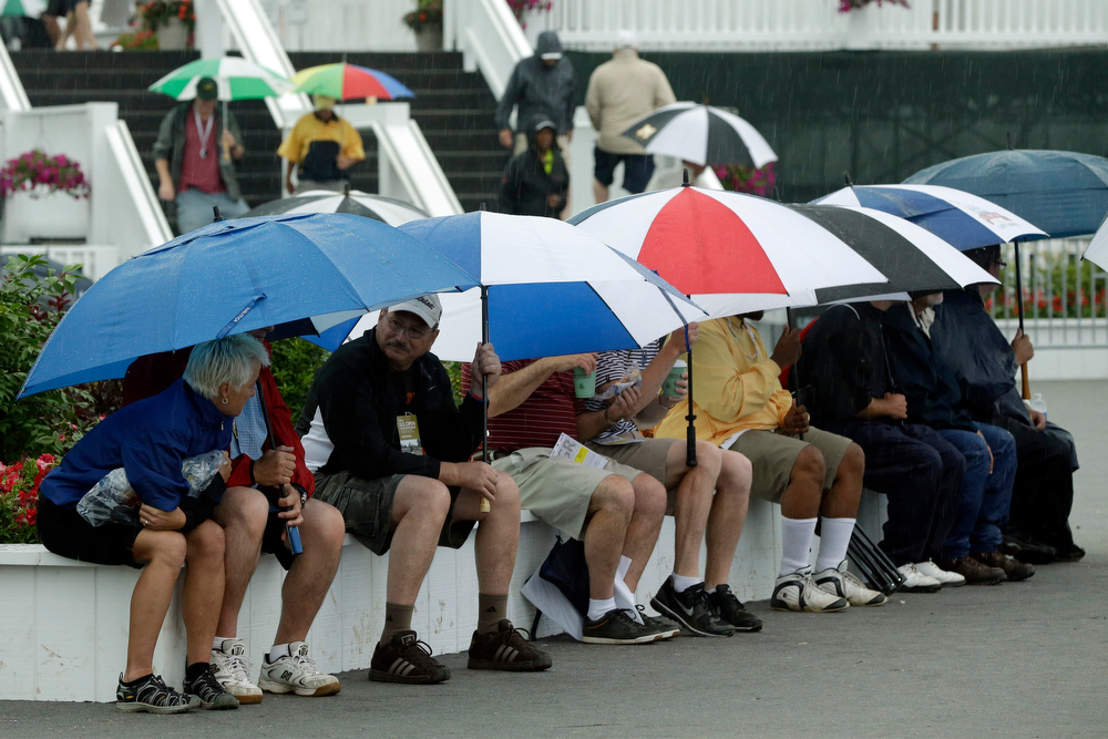 . Spectators wait out a weather delay during the first round of the U.S. Open golf tournament at Merion Golf Club, Thursday, June 13, 2013, in Ardmore, Pa. (AP Photo/Gene J. Puskar)