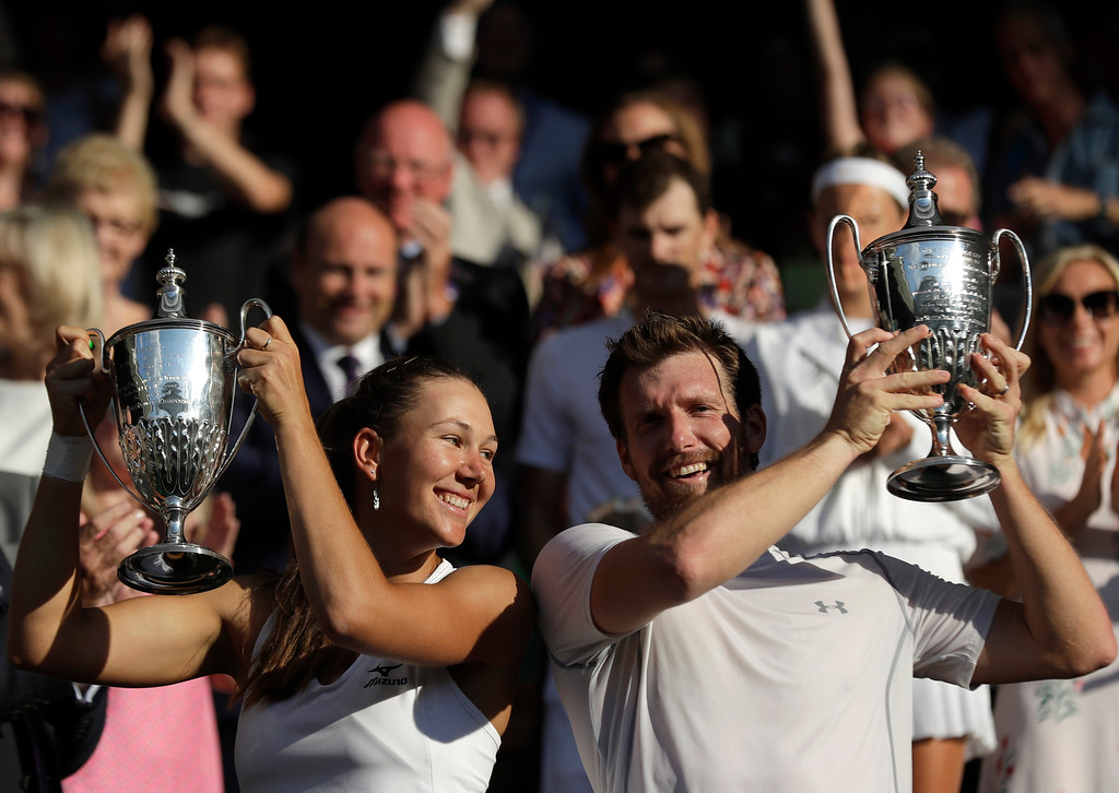 . Nicole Melichar, left, of the United States and Austria\'s Alexander Peya, lift the trophies after winning the mixed doubles final match against Britain\'s Jamie Murray and Victoria Azarenka of Belarus, at the Wimbledon Tennis Championships, in London, Sunday July 15, 2018.(AP Photo/Ben Curtis)