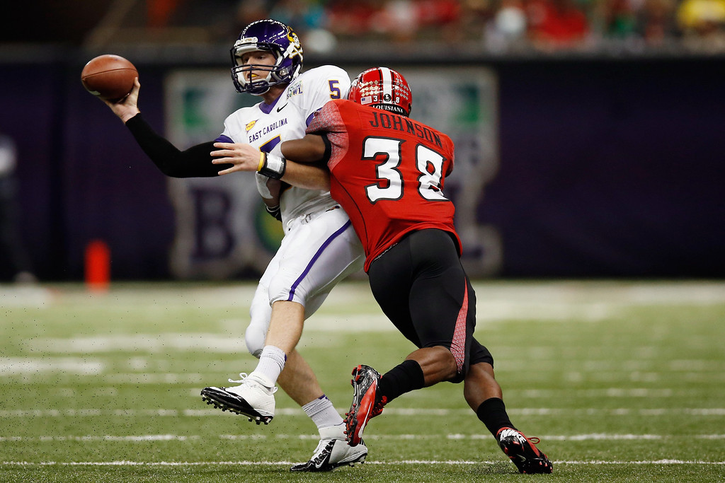 . Shane Carden #5 of the East Carolina Pirates is tackled by Trae Johnson #38 of the Louisiana-Lafayette Ragin Cajuns during the R+L Carriers New Orleans Bow at the Mercedes-Benz Superdome on December 22, 2012 in New Orleans, Louisiana.  (Photo by Chris Graythen/Getty Images)