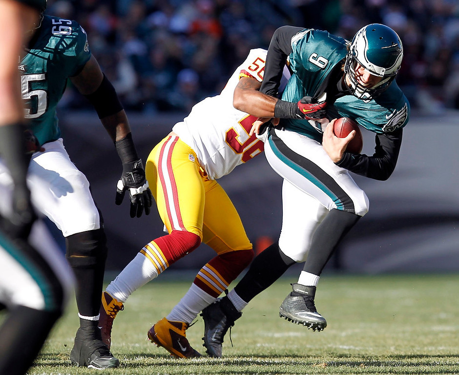 . Philadelphia Eagles quarterback Nick Foles (9) is sacked by the Washington Redskins linebacker Perry Riley (56) during the first quarter of their NFL football game in Philadelphia, Pennsylvania December 23, 2012. REUTERS/Tim Shaffer