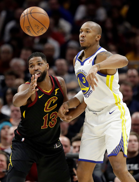. Golden State Warriors\' David West (3) passes against Cleveland Cavaliers\' Tristan Thompson (13) in the first half of an NBA basketball game, Monday, Jan. 15, 2018, in Cleveland. (AP Photo/Tony Dejak)