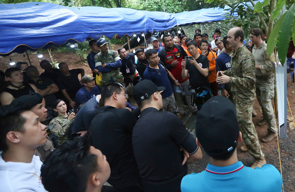 . Personnels, right, of U.S. Special Operations Command Pacific Search and Rescue team meet with rescue teams from China, Thailand and Australia as they conduct search operation for missing 12 boys and their soccer coach, in Mae Sai, Chiang Rai province, in northern Thailand, Monday, July 2, 2018. Rescue divers are advancing in the main passageway inside the flooded cave in northern Thailand where the boys and their coach have been missing more than a week. (AP Photo/Sakchai Lalit)
