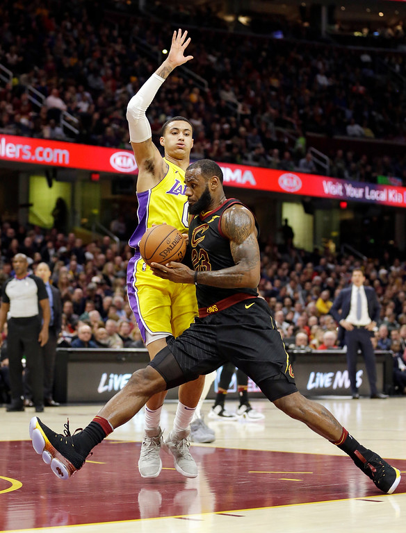 . Cleveland Cavaliers\' LeBron James, right, drives past Los Angeles Lakers\' Kyle Kuzma in the first half of an NBA basketball game, Thursday, Dec. 14, 2017, in Cleveland. (AP Photo/Tony Dejak)