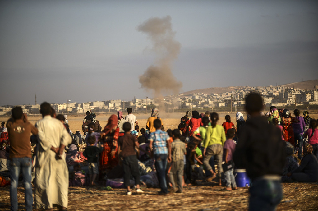 . Syrian Kurds look at smoke billowing after a mortar hit the land near the Syrian border at the southeastern town of Suruc in Sanliurfa province, on September 20, 2014. Tens of thousands of Syrian Kurds flooded into Turkey on September 20, fleeing an onslaught by the jihadist Islamic State group that prompted an appeal for international intervention.  BULENT KILIC/AFP/Getty Images