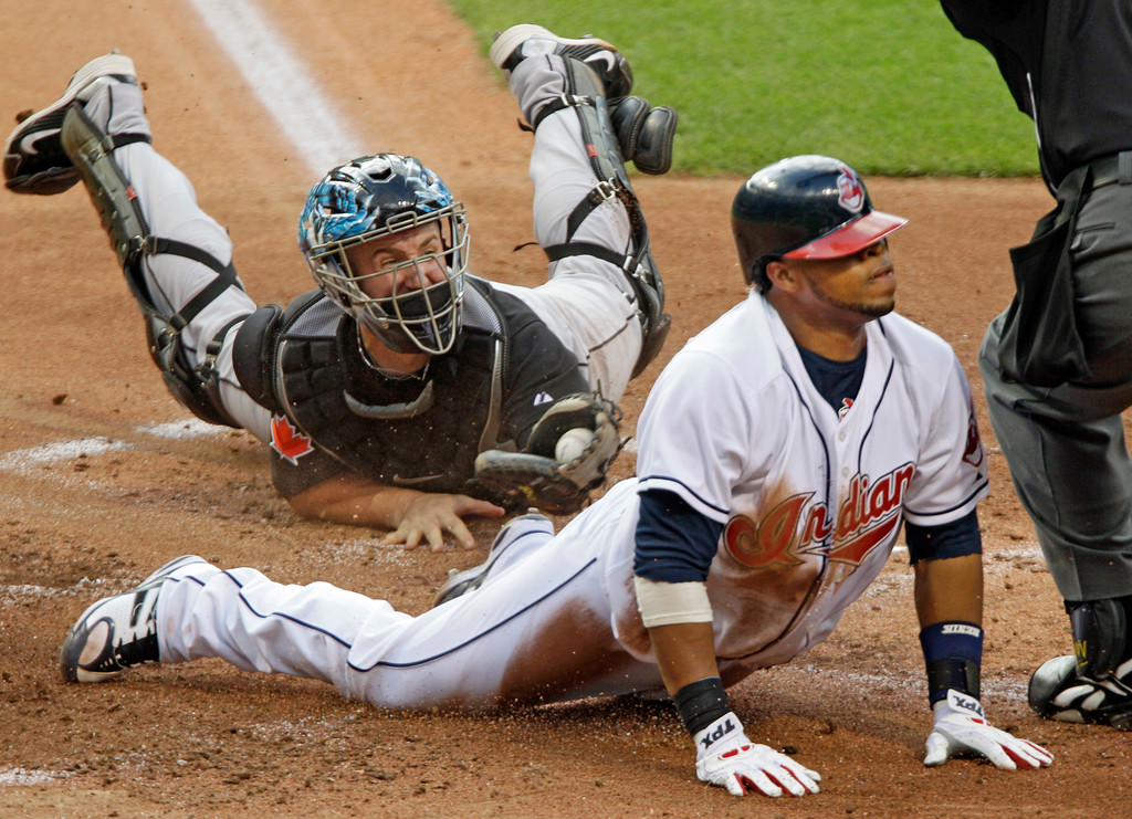 . Cleveland Indians\' Carlos Santana, right, slides home to score past the tag from Toronto Blue Jays catcher John Buck in the first inning of a baseball game Monday, June 28, 2010, in Cleveland. (AP Photo/Mark Duncan)