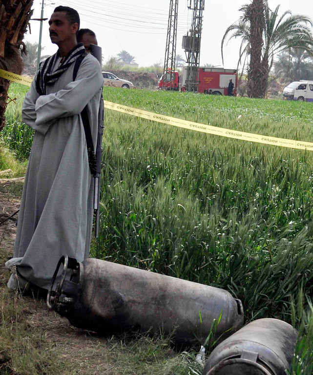 . A man stands beside gas tanks amid the wreckage of a hot air balloon that crashed in Luxor February 26, 2013. Eighteen Asian and European tourists died when a hot air balloon crashed early on Tuesday near the ancient Egyptian town of Luxor following a mid-air gas explosion, officials said. REUTERS/Stringer