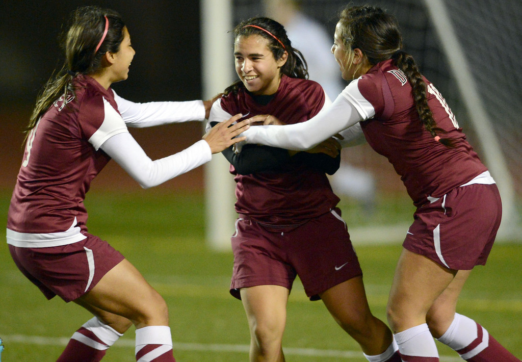 . Downey\'s Maritza Acuna (9) and Krista Velasco (10) celebrate Tara Kazimi\'s (22) goal against Torrance in the final two minutes that would ensure a win in the CIF SS Division IV quarterfinal game Thursday at Zamperini Field. Downey won the game 3-1. 20130221 Photo by Steve McCrank / Staff Photographer