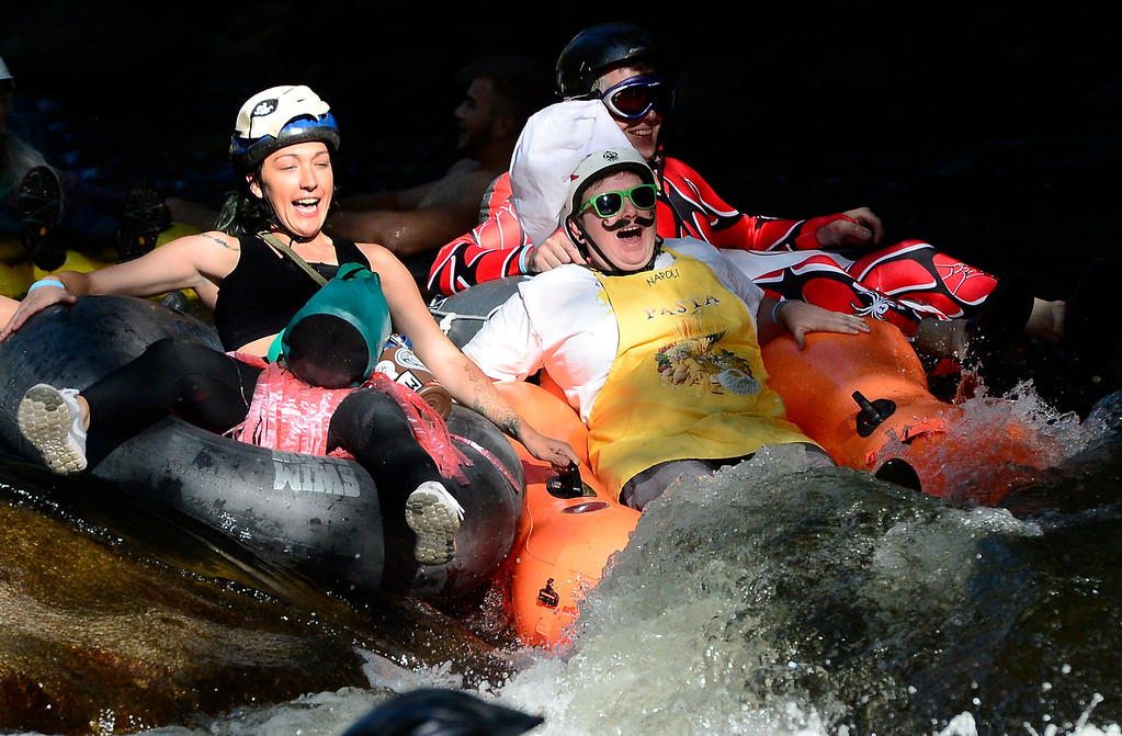 . Chrissy Gedenberg, sporting a traditional chef\'s hat, hits the first rapids as she an other tubers start out at Eben G. Fine Park during the 11th Annual Tube to Work Day on Boulder Creek on Wednesday morning.  Paul Aiken Staff Photographer July 11 2018