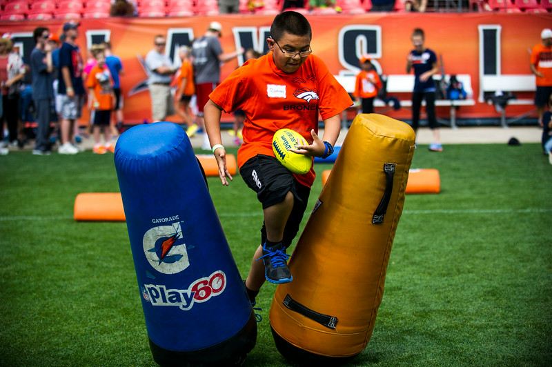 . Ramon Balderas-Soto runs through drills during the National Sports Center for the Disabled\'s Denver Broncos Ability Clinic at Sports Authority Field at Mile High on Tuesday, July 08, 2014 in Denver, CO. (Photo by Kent Nishimura/The Denver Post)
