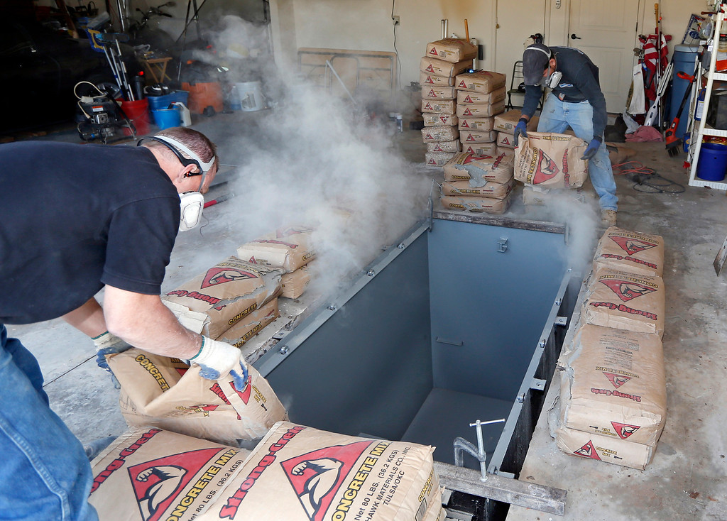 . In this Thursday, May 1, 2014 photo, Jim Hohnsbehn, left, and Jacob Ortiz, of Thunderground Storm Shelters, pour bags of concrete around the sides of a storm shelter during an installation into the garage of a residence in Oklahoma City.  (AP Photo/Sue Ogrocki)