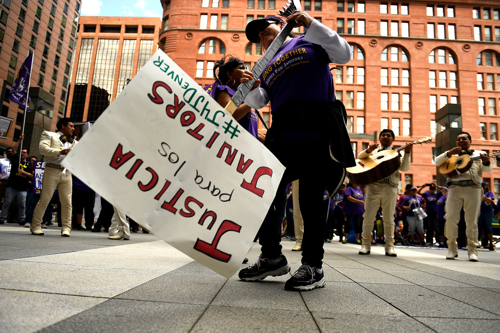 . Denver, CO - ARRIL 14: Francesca Dominguez 50, a janitor here for the last 8 years using her sign to sweep as the Mariachi Musicians play at Republic Plaza in downtown Denver. The low wage janitors kicked off their contract campaign with a rally at Civic Center Park�s Veterans Memorial in downtown and a march past all the buildings where they do their work in Denver. The janitors were joined by local care workers, Fast food, delivery persons and service workers during their  Underpaid Fight for $15 march. April 14, 2016 in Denver, CO. (Photo By Joe Amon/The Denver Post)