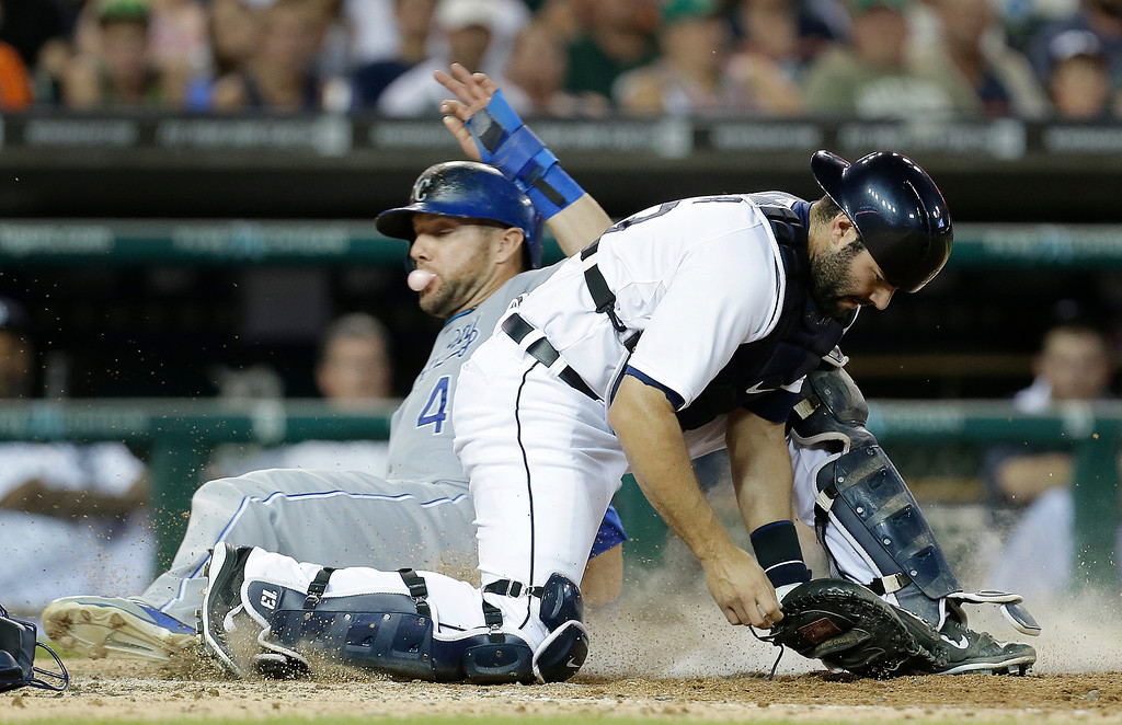 . Kansas City Royals\' Alex Gordon slides safely into home plate as Detroit Tigers catcher Alex Avila can\'t handle the throw on a error by pitcher Evan Reed in the seventh inning of a baseball game in Detroit, Monday, June 16, 2014. Mike Moustakas was safe at first base on the throwing error at home plate. (AP Photo/Paul Sancya)