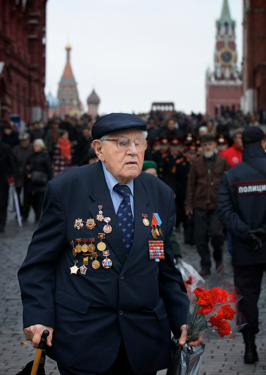 . Russian WWII veteran Vladimir Vermel, 91, leaves Red Square after watching a parade in Moscow, Russia, Thursday, Nov. 7, 2013, with  St. Basil Cathedral, center, and Spassky Tower, right, in the background. Thousands of Russian soldiers and military cadets marched across Red Square to mark the 72nd anniversary of a historic World War II parade. The show honored the participants of the Nov. 7, 1941 parade who then headed directly to the front to defend Moscow from the Nazi forces. (AP Photo/Alexander Zemlianichenko)