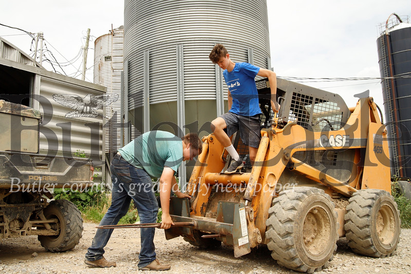 Tyler (left) and Austin Miller prep their skid loader to move hay bales for wrapping. Seb Foltz/Butler Eagle