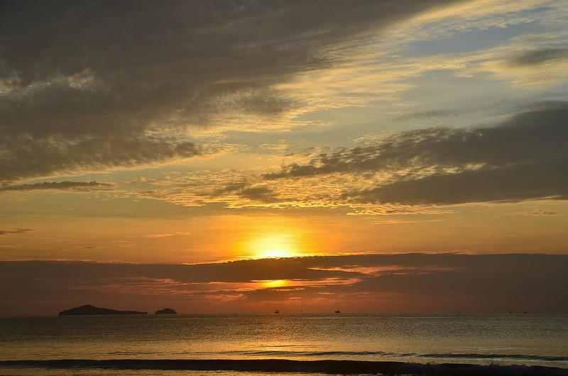 Colourful golden stratocumulus cloudy tropical ocean sunrise seascape. Thailand.