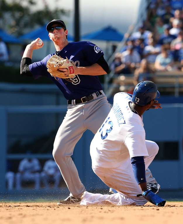 . LOS ANGELES, CA - JULY 13:  Second baseman DJ LeMahieu #9 of the Colorado Rockies throws to first to complete a double play after forcing out Hanley Ramirez #13 of the Los Angeles Dodgers in the fourth inning at Dodger Stadium on July 13, 2013 in Los Angeles, California.  (Photo by Stephen Dunn/Getty Images)
