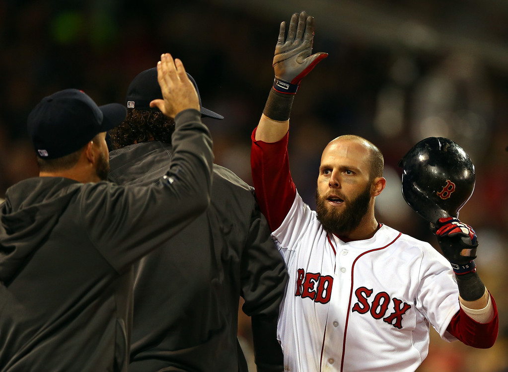 . Dustin Pedroia #15 of the Boston Red Sox returns to the dugout after scoring in the first inning against the St. Louis Cardinals during Game One of the 2013 World Series at Fenway Park on October 23, 2013 in Boston, Massachusetts.  (Photo by Elsa/Getty Images)