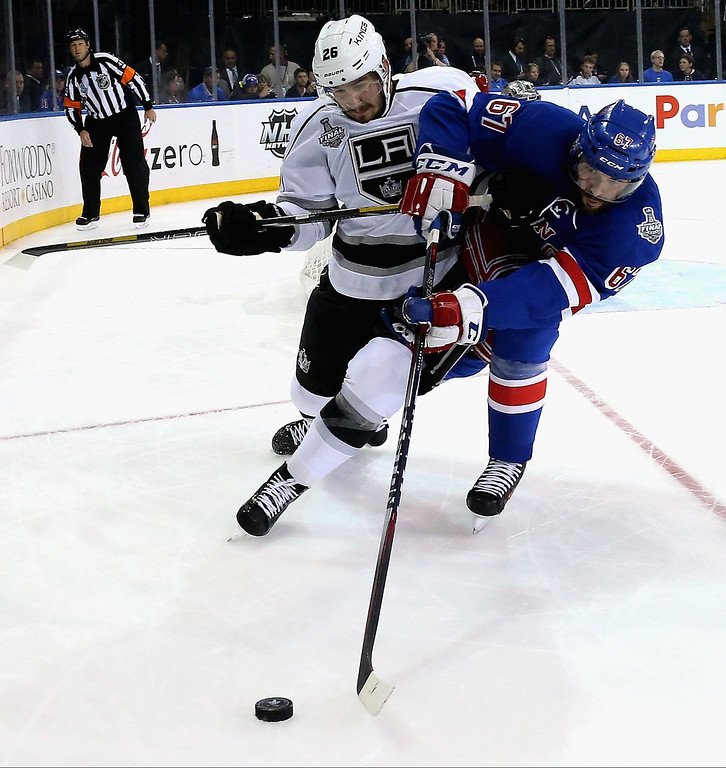 . Slava Voynov #26 of the Los Angeles Kings battles Benoit Pouliot #67 of the New York Rangers for the puck during the second period of Game Three of the 2014 NHL Stanley Cup Final at Madison Square Garden on June 9, 2014 in New York, New York.  (Photo by Bruce Bennett/Getty Images)