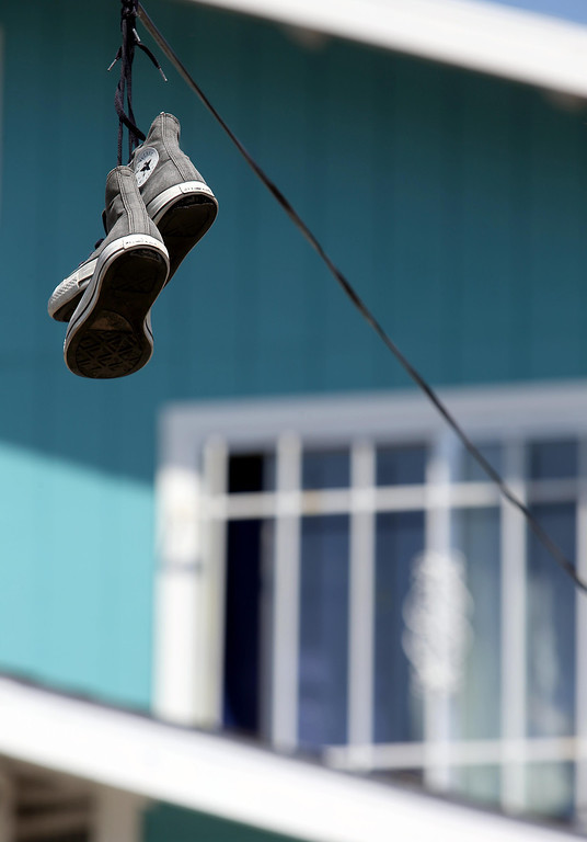. A pair of sneakers hang from a wire on Holway Street as barred windows are seen in the backround in Oakland, Calif., on Friday, April 12, 2013.  (Jane Tyska/Staff)