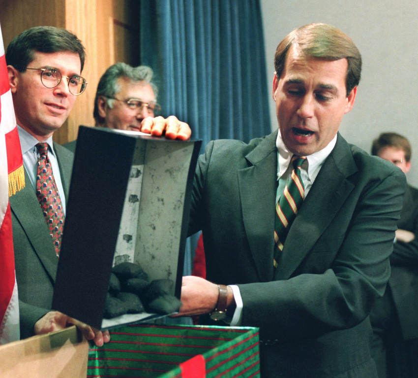 . Rep. John Boehner, R-Ohio, dumps out coal, which he called a Christmas gift to President Clinton, during a Capitol Hill news conference Thursday Dec. 21, 1995 to discuss the federal budget. The White House and Congressional Republicans labored Thursday to restart balanced budget talks and grappled with the impact of a six-day partial government shutdown. Rep. Bill Paxon, R-N.Y., left, and House Majority Leader Dick Armey of Texas look on. (AP Photo/Denis Paquin)