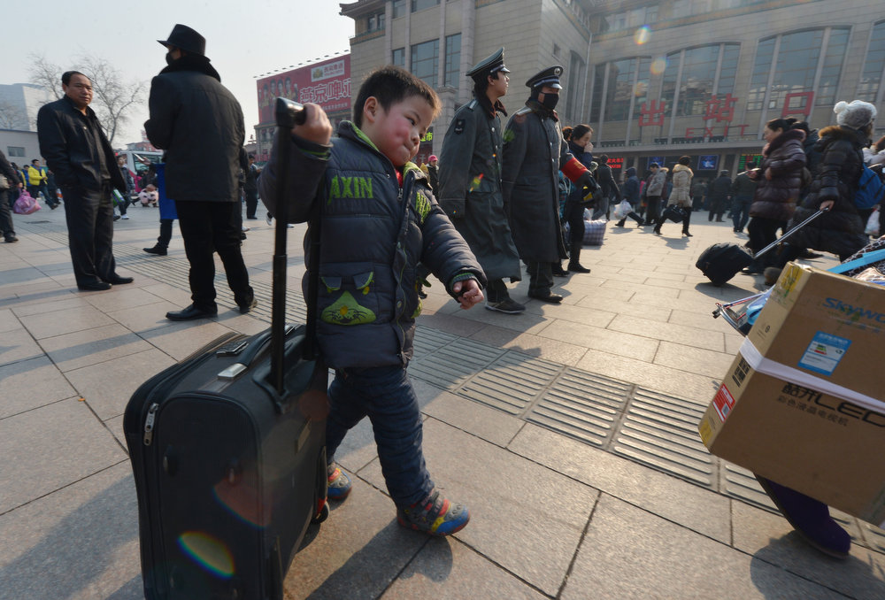 . Chinese travelers arrive to board trains as the annual Lunar New Year exodus begins at Beijing train station on January 26, 2013.   The holiday also known as the Spring Festival sees tens of millions of migrant workers who provide the labour in the country\'s prosperous cities return to their villages and towns to spend time with the families left behind.    MARK RALSTON/AFP/Getty Images