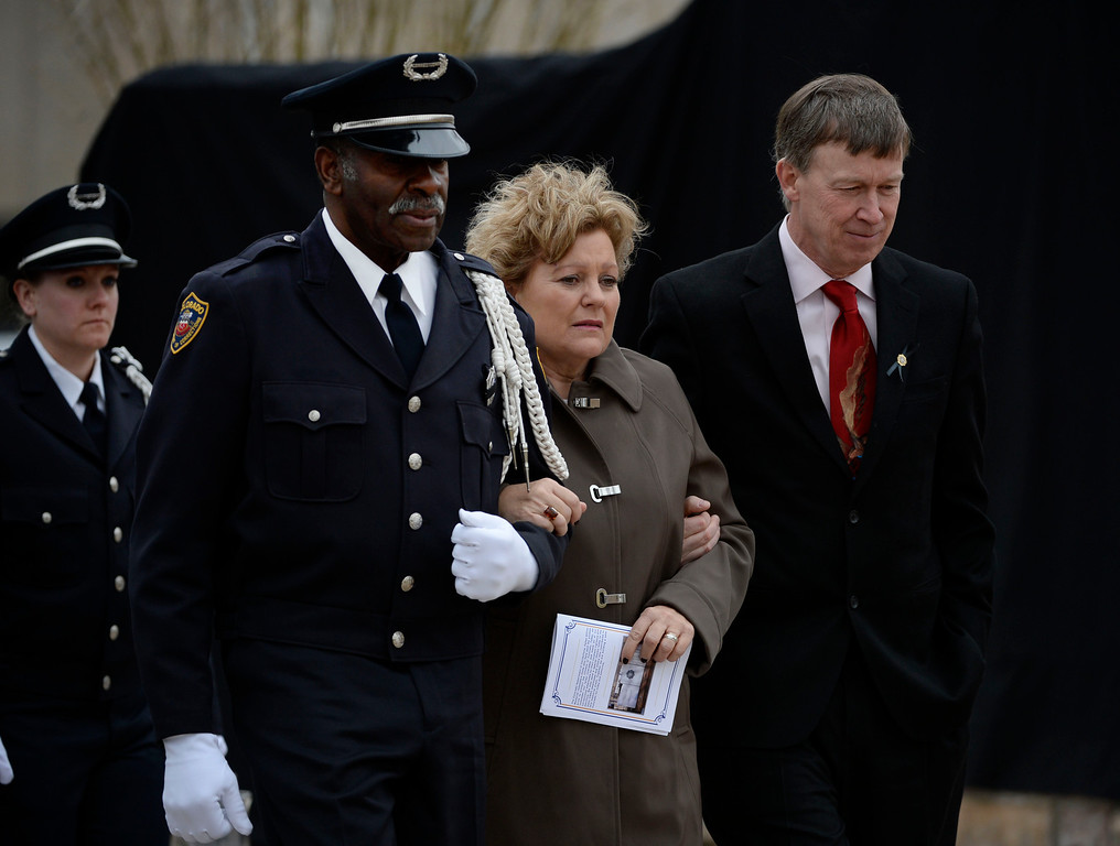 . Colorado Department of Corrections Honor Guard member, Harry Campbell, left, along with Colorado Governor, John Hickenlooper, right, escort Lisa Clements, center, to a tree dedication at the Colorado Department of Corrections Fallen Officer Memorial honoring Lisa\'s husband, the head of the DOC, Tom Clements, at the Territorial Correctional Facility park Saturday morning, March 15, 2014.  (Photo By Andy Cross / The Denver Post)