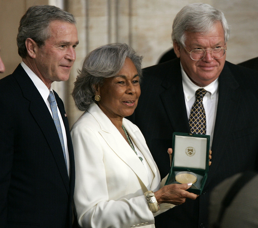. Flanked by U.S. President George W. Bush (L) and Speaker of the House Dennis Haster (R-IL) (R), Rachel Robinson (C), widow of baseball player Jackie Robinson receives the Congressional Gold Medal that is presented to her husband during a ceremony March 2, 2005 on Capitol Hill in Washington, DC. Jackie Robinson was recognized for his legendary baseball career, his lifetime of breaking down barriers and his unending fight for justice.  (Photo by Alex Wong/Getty Images)