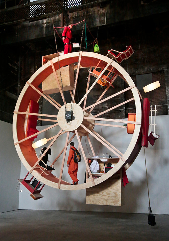 ". The performance art ""In Orbit,\"" a 25-foot wheel made from wood, steel, and furniture, is home for artists Ward Shelley, top, and Alex Schweder, bottom, for 10 days at the Boiler gallery in the Brooklyn borough of New York, Tuesday, March 4, 2014. They will share two living units arrayed over the hamster-wheel-like sculpture, with Shelly living on the outside and Schweder on the inside. The structure will remain on view through April 5.  (AP Photo/Bebeto Matthews)"