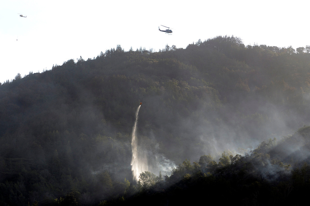 . A helicopter makes a water drop on Pfeiffer Ridge above Fernwood in Big Sur, Calif. on Thursday December 19, 2013. (Photo David Royal/ Monterey County Herald)