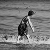 A young boy jumping waves on the beach in Gibraltar during the winter months.