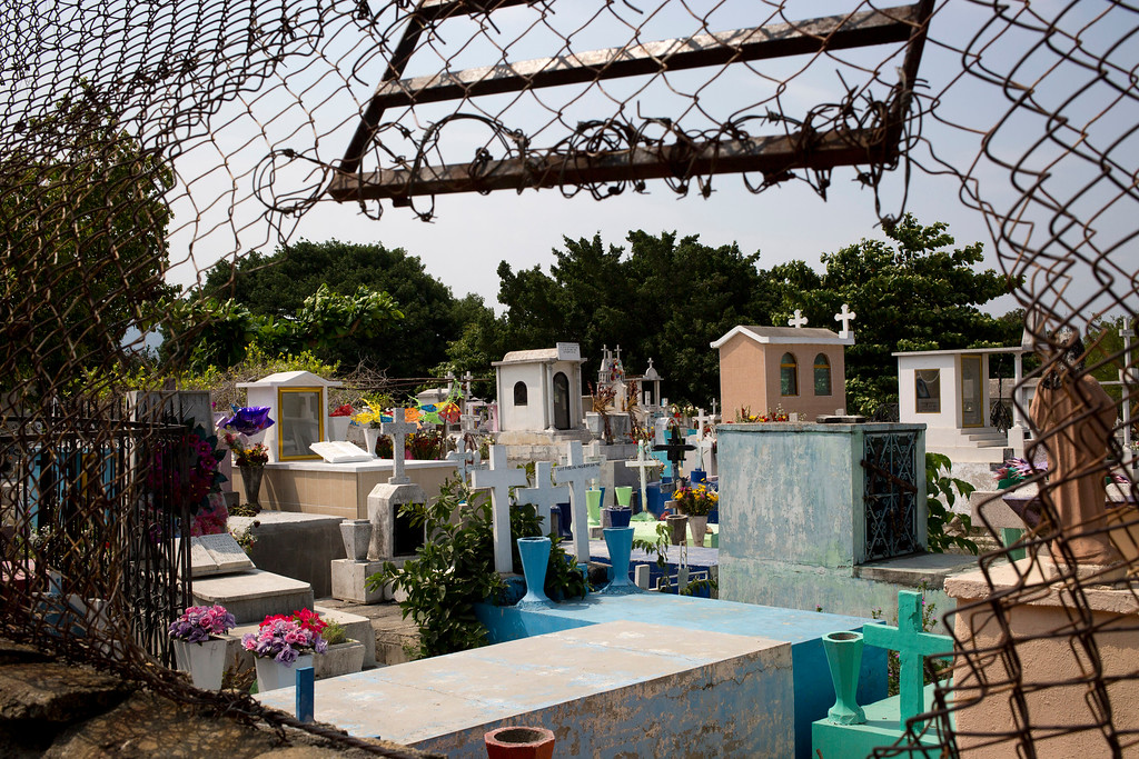 . In this May 11, 2016 photo, the fence separating the street from the Las Cruces neighborhood cemetery has been ripped open, in Acapulco, Mexico. Violence gripping this once-glamorous resort and its neighborhoods has seen an upsurge in the last months. According to estimates of local press more than 300 murders by gunfire have occurred in the city since the beginning of the year up to date. (AP Photo/Enric Marti)