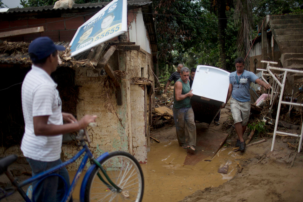 Description of . Residents salvage a fridge from a home flooded by heavy rains in the Xerem neighborhood, about 31 miles north of Rio de Janeiro, Brazil, Thursday, Jan. 3, 2013. Nearly 8.5 inches of rain fell in just 24 hours in the mountainous region north of Rio. Hard rains in Brazil are creating a state of alert in Rio de Janeiro and in nearby spots where flood-triggered mudslides have killed hundreds in recent years.  (AP Photo/Felipe Dana)