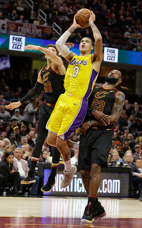 . Los Angeles Lakers\' Kyle Kuzma (0) shoots against Cleveland Cavaliers\' Kyle Korver (26) and LeBron James (23) in the second half of an NBA basketball game, Thursday, Dec. 14, 2017, in Cleveland. (AP Photo/Tony Dejak)
