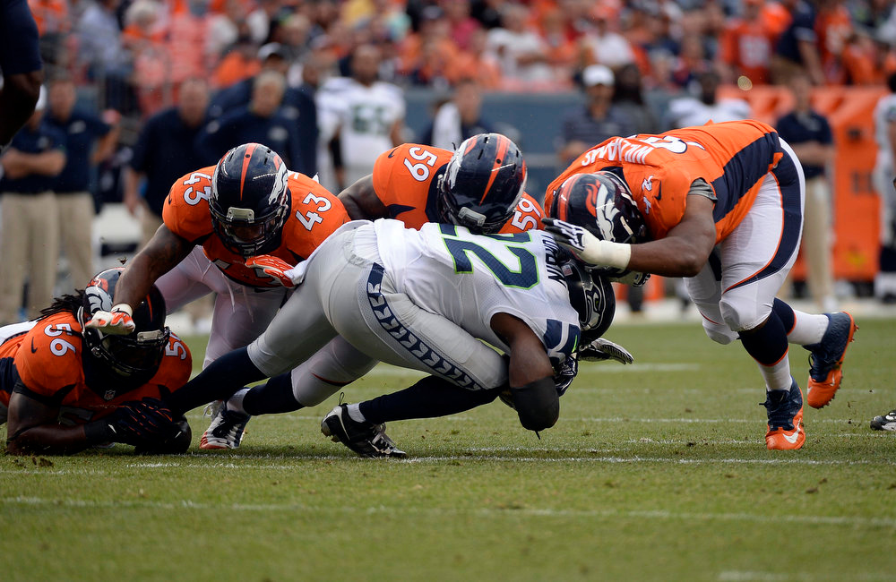 . Running back Robert Turbin (22) of the Seattle Seahawks gets taken down by outside linebacker Nate Irving (56), strong safety T.J. Ward (43), outside linebacker Danny Trevathan (59), and defensive tackle Sylvester Williams (92) of the Denver Broncos during the first quarter.  The Denver Broncos vs the Seattle Seahawks At Sports Authority Field at Mile High. (Photo by John Leyba/The Denver Post)