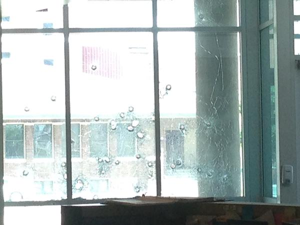. In this handout photo provided by the Dallas Police Department bullet holes are seen in the glass windows of the Dallas Police Headquarters on June 13, 2015 in Dallas, Texas.  A single gunman opened fire on the building early Saturday morning, reportedly unleashing multiple rounds and planting explosive devices around the station. No injuries have been reported. (Photo by Dallas Police Department via Getty Images)